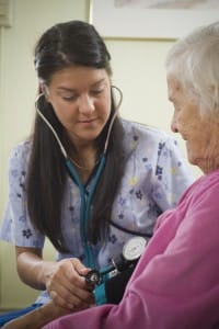 nurse helping older woman through senior home health care services